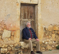 Don Harris sitting on a ledge in a rustic village