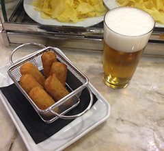 a basket of croquetas and a small glass of beer