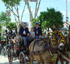 people wearing traditional feria dress, riding in carriages