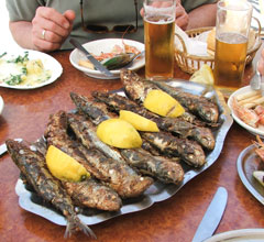 plate of whole fried fish with lemon wedges