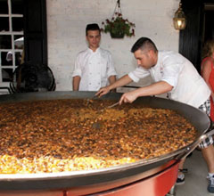 two men cooking a giant paella
