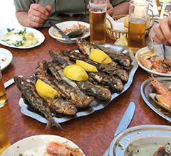 plate of whole fried fish topped with lemons