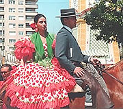 lady and man on horseback wearing traditional feria clothing